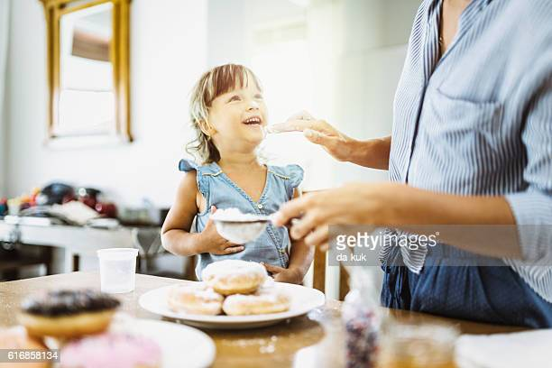 Mother and daughter making sweet donuts in the kitchen