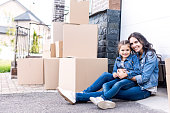 young mother and daughter sitting on floor in front of garage gate with stacks of boxes
