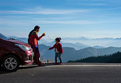 Mother and daughter enjoying the road trip and winter vacation. Car travel vacation concept photo against Himalayan mountain in the background.