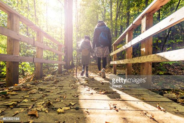 Mother and daughter on a sunny autumn dayin the forest walking over wooden bridge