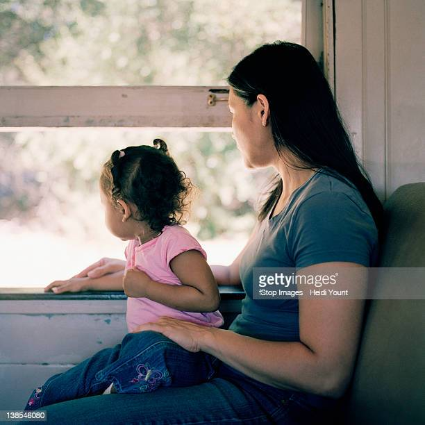 A mother and daughter on a train, looking through window