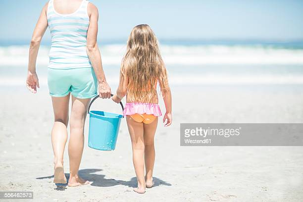 Mother and daughter on beach walking with a bucket