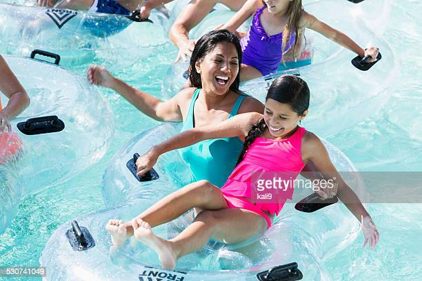 Mother and daughter on innertube at water park