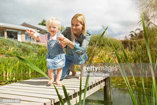 Mother and daughter (12-23 months) on jetty : Stock Photo