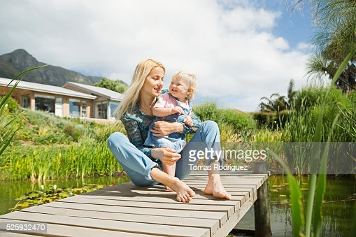 Mother and daughter (12-23 months) on jetty : Stock-Foto
