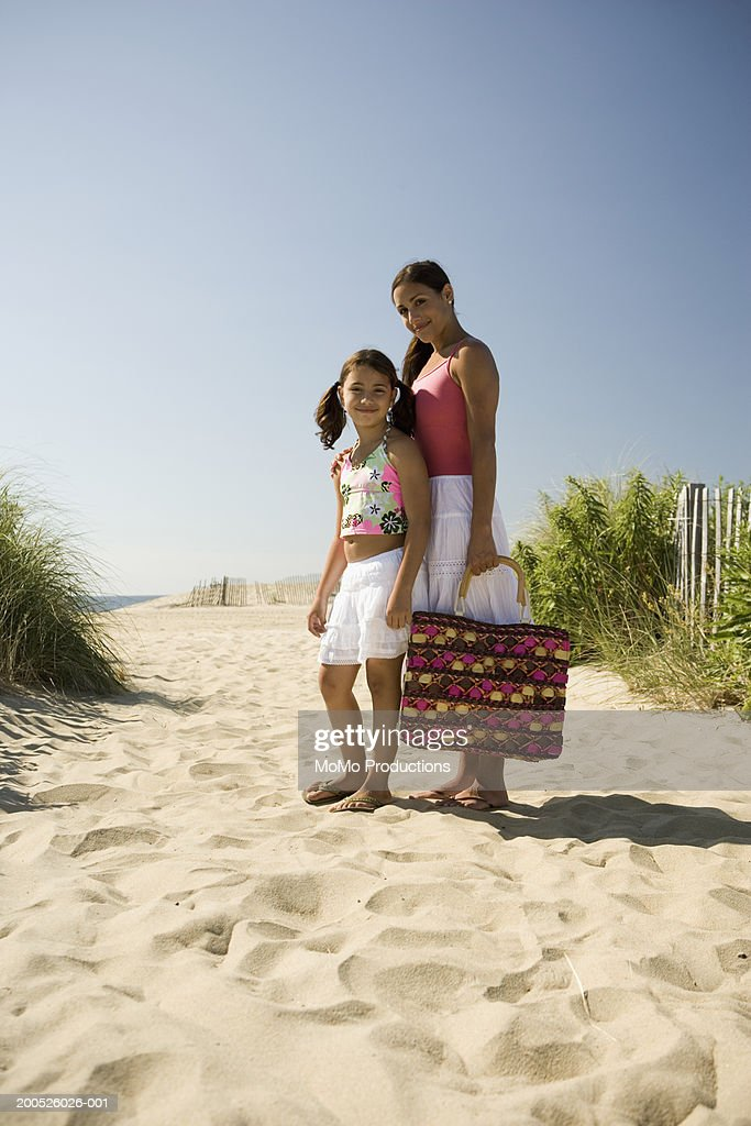 Mother and daughter (8-10) on path to beach, portrait : Stock Photo