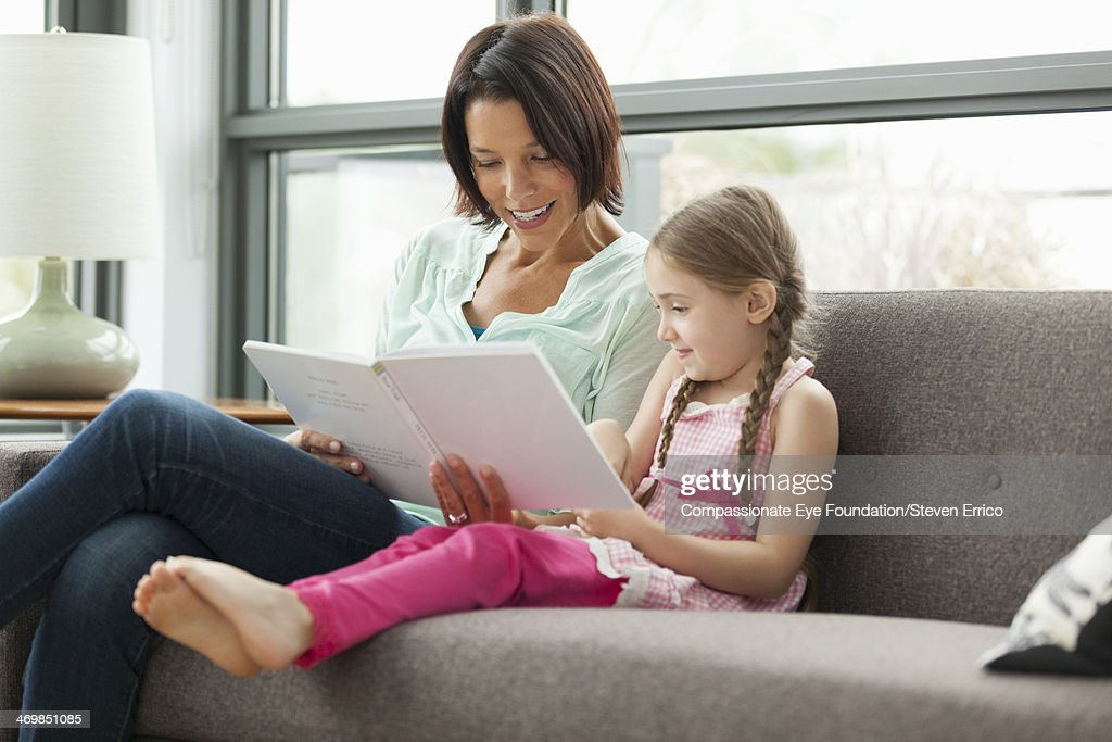 Mother and daughter on sofa reading book : Stock Photo