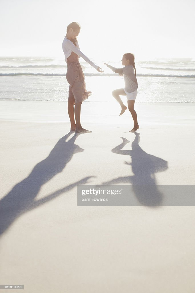 Mother and daughter on sunny beach : Stock Photo