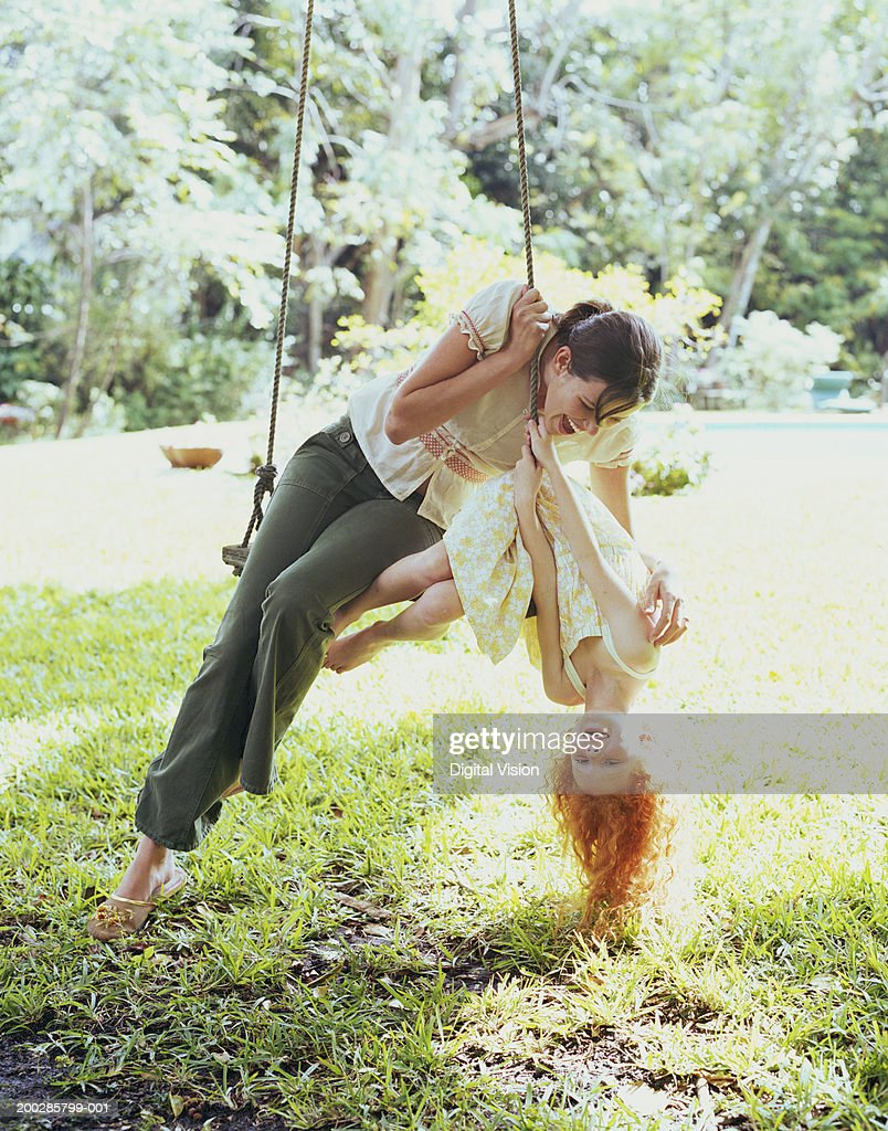 Mother and daughter (6-8) on swing, daughter tipping upside down