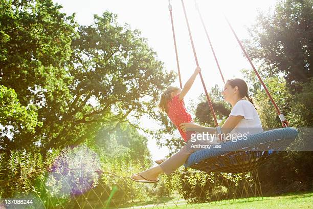 Mother and daughter on swing in sunny park