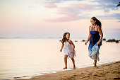 Mother and daughter playing together on the beach in the tropical climate of Kauai, Hawaii