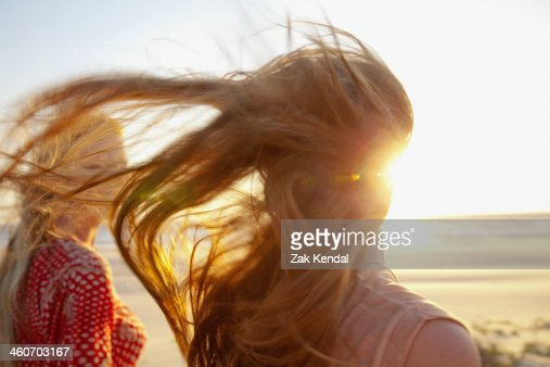 Mother and daughter on windy beach, close up