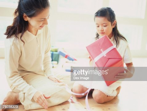 Mother and daughter opening a present : Stock Photo