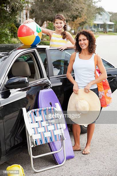 Mother and daughter packing car for trip to beach