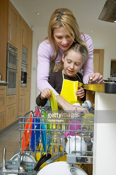 Mother and daughter (5-7) packing dishwasher