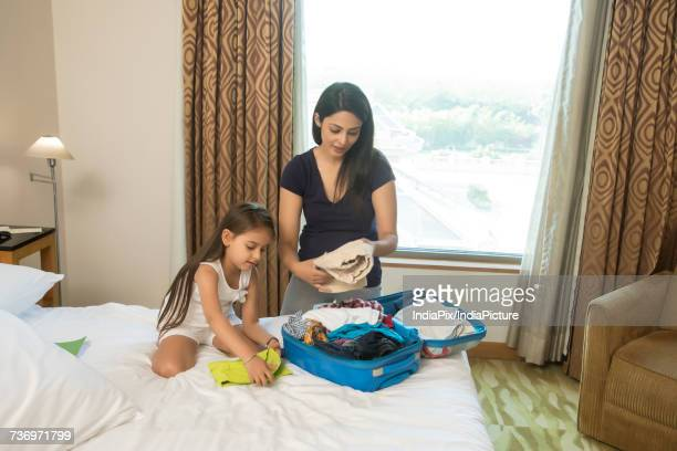 Mother and daughter packing for vacation on bed