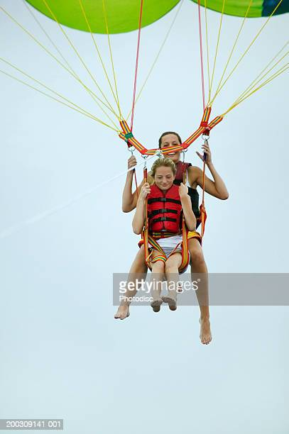 Mother and daughter (8-9), parasailing, low angle view
