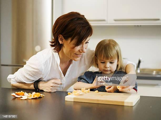 Mother and daughter peeling orange