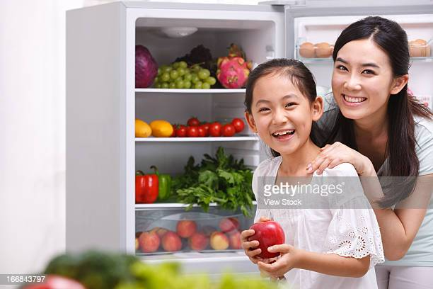 Mother and daughter picking fruit from bridge