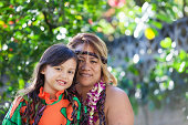Hawaiian mother and daughter in traditional Hawaiian clothing with leis around their necks