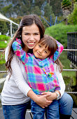 Young colombian mother and her daughter togheter on a city park.