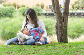 Young colombian mother and her daughter looking at each other and sitting on the grass on a city park.