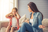Beautiful young mother is scolding her daughter while sitting on sofa at home. Girl is covering her ears