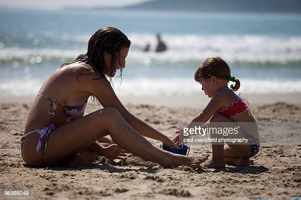 Mother and daughter play on sandy beach together