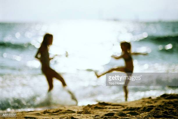 Mother and daughter playing at beach, silhouette (defocussed)