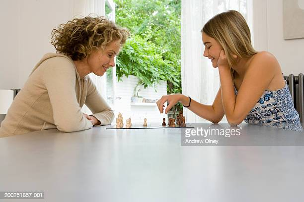 Mother and daughter (13-15) playing chess, smiling, side view