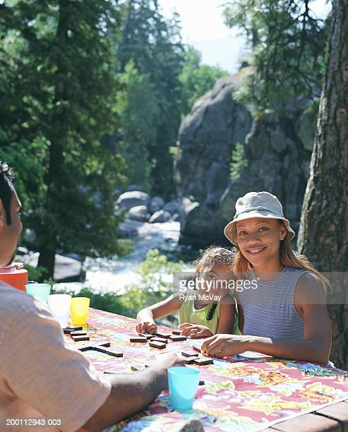 Mother and daughter (5-7) playing dominoes at picnic table with father