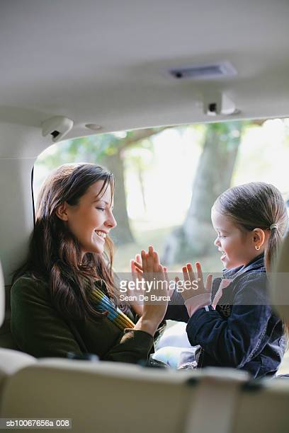 Mother and daughter (6-7) playing in back of car