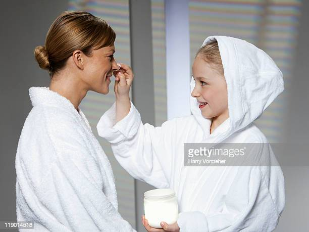 Mother and daughter playing in bathrobes