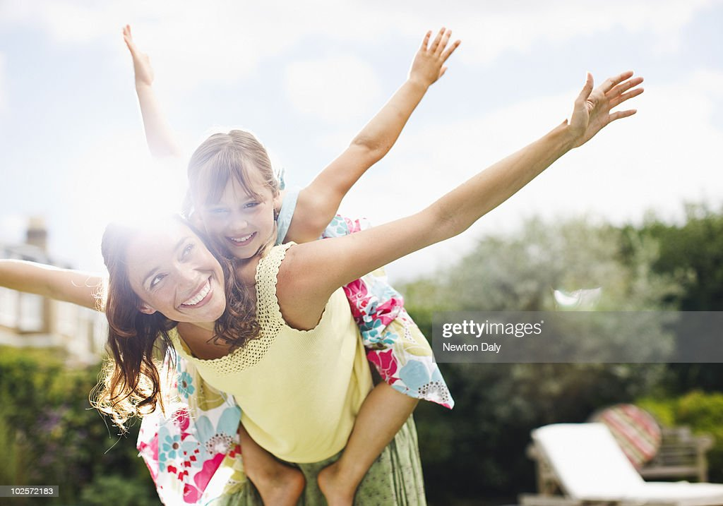 Mother and daughter (8-9) playing in garden : Stock Photo