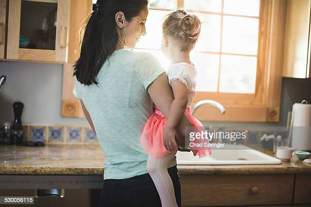 Mother and daughter playing in kitchen