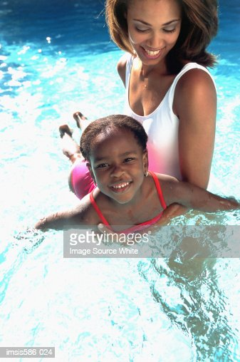 Mother and daughter playing in pool : Foto de stock
