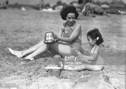Mother and daughter (4-5) playing in sand on beach, (B&W) : Stock Photo