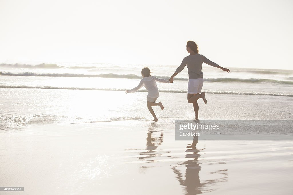 Mother and daughter playing in surf at beach : Stock Photo