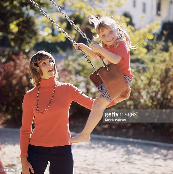 Mother and daughter playing in swing set