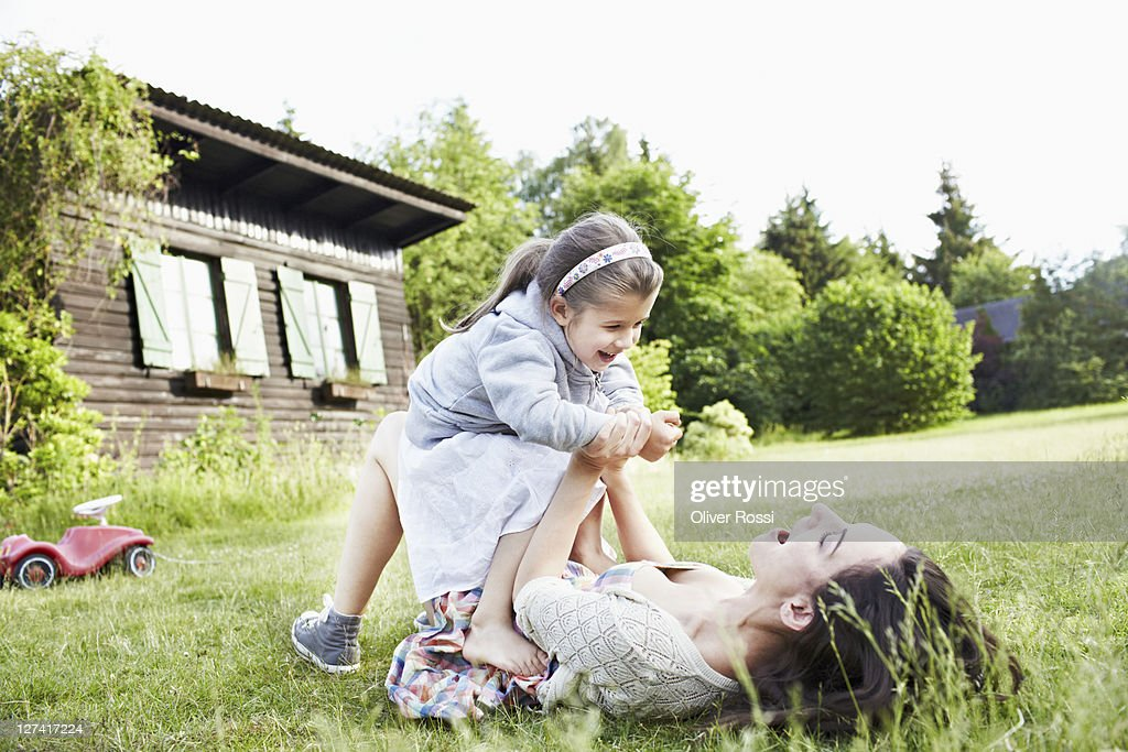 mother and daughter playing in the garden : Stock Photo