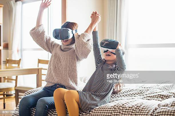 Mother and daughter playing in virtual reality glasses in bedroom