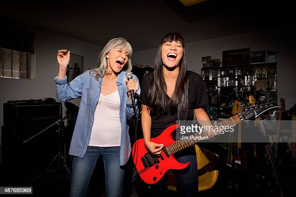 Mother and daughter playing music guitar in basement