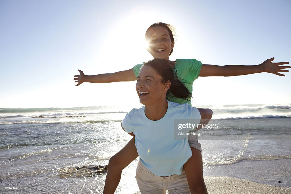 Mother and daughter playing on beach : Stock Photo