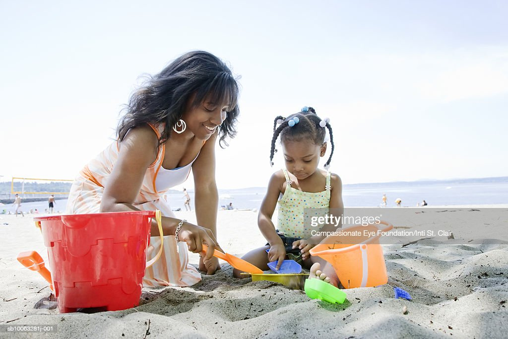 Mother and daughter (2-3) playing on beach : Stock Photo