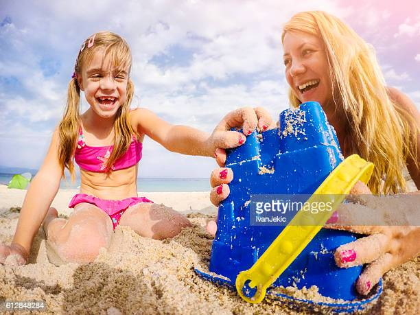 Mother and daughter playing on beach with sand pail