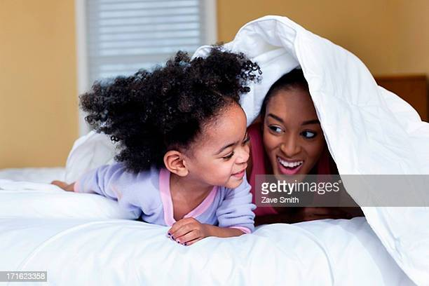 Mother and daughter playing on bed hiding under duvet