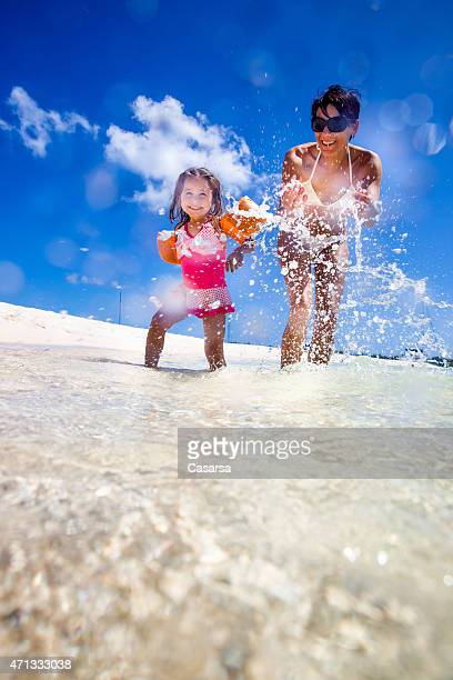 Mother and daughter playing on idylic beach