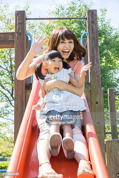 Mother And Daughter Playing On Slide
