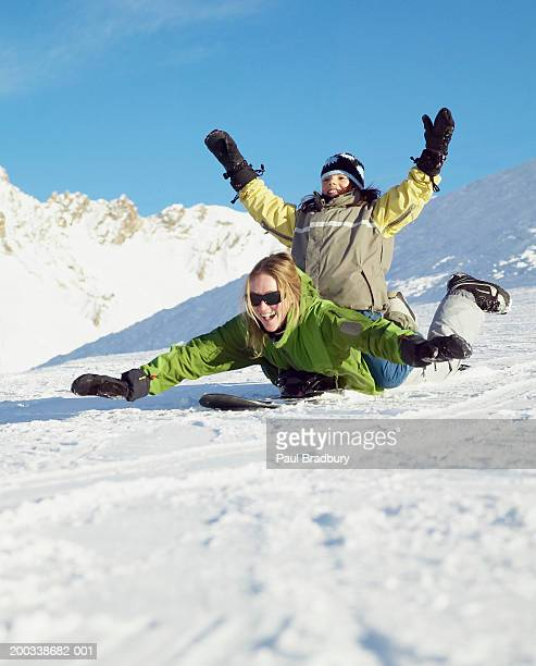 Mother and daughter (9-11) playing on snowboard, arms outstretched