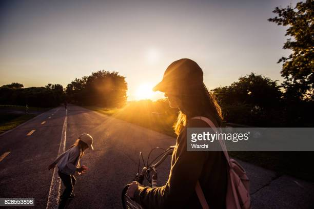 Mother and daughter playing on the bicycle lane at sunset